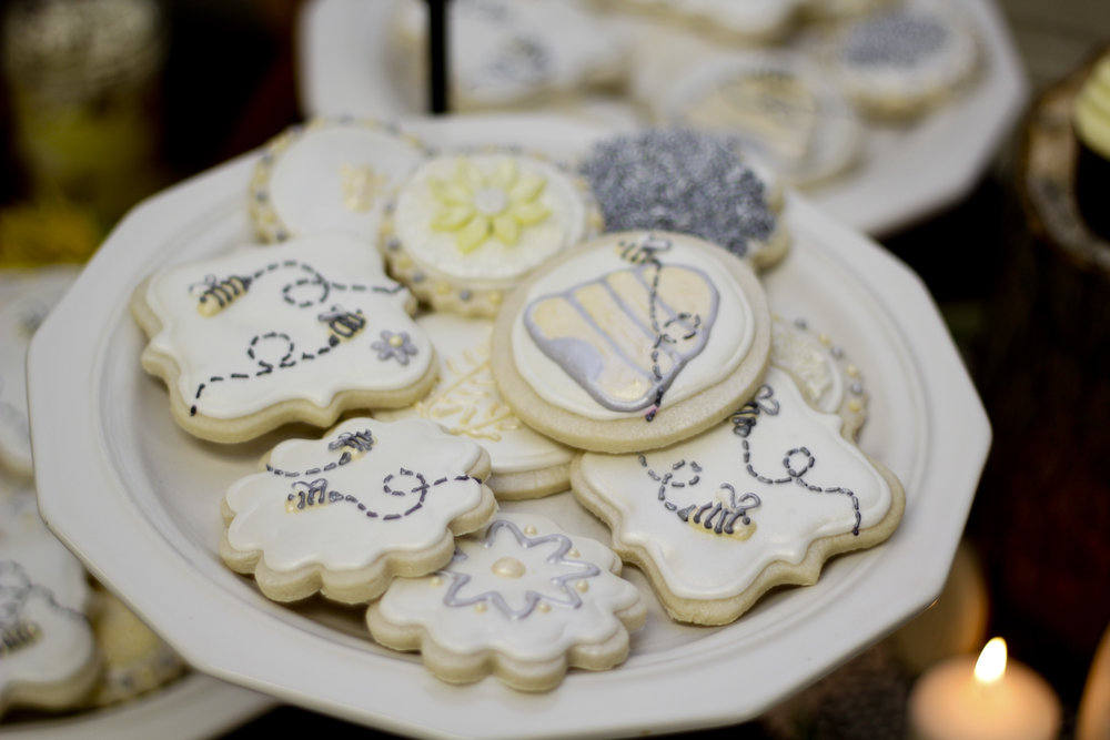 Cookies for a pooh bear themed baby shower. Shortbread cookies with royal icing decorated with beehives, bumblebees, flowers, and sprinkles.