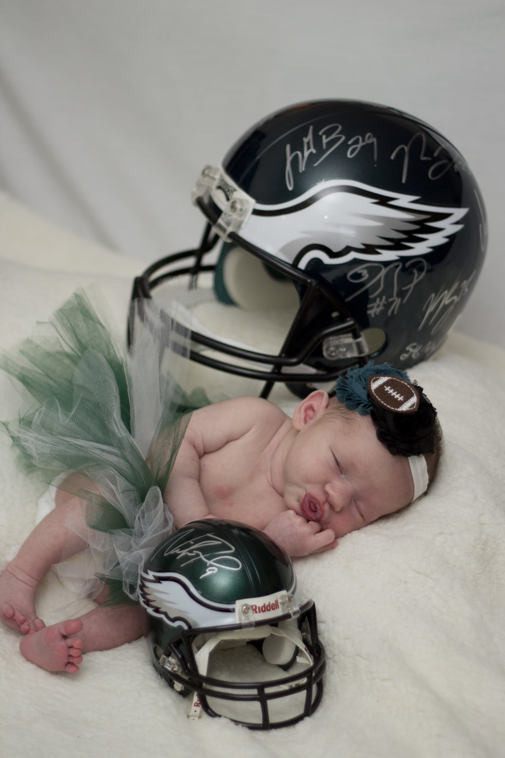 Sweet newborn baby girl session in Southern New Jersey. Look at that newborn baby with all her Eagles football gear! The little helmet is signed by Nick Foles and the larger is signed by the rest of the Super Bowl LII CHAMPS! Go Birds!