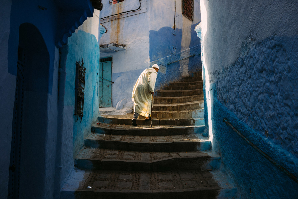 An elderly man slowly climbing the stairs of the Blue City.