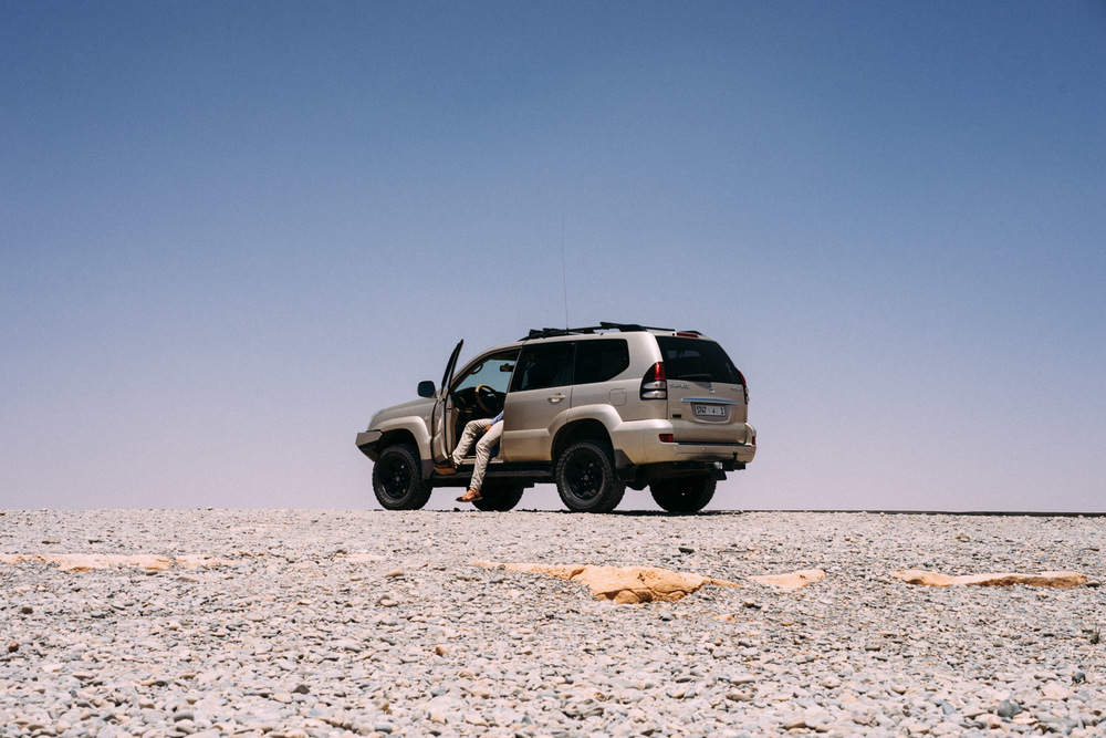 Hassan, our guide waits in his car during a pit stop on our way into the Sahara.