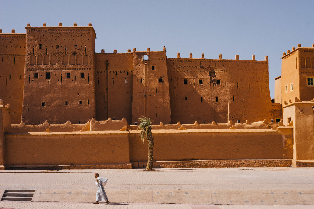 A man walking past a typical mud brick fortress on the way to Ait Ben Haddou.