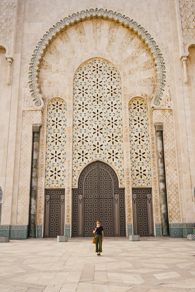 Dwarfed by one of the massive entryways into the mosque.