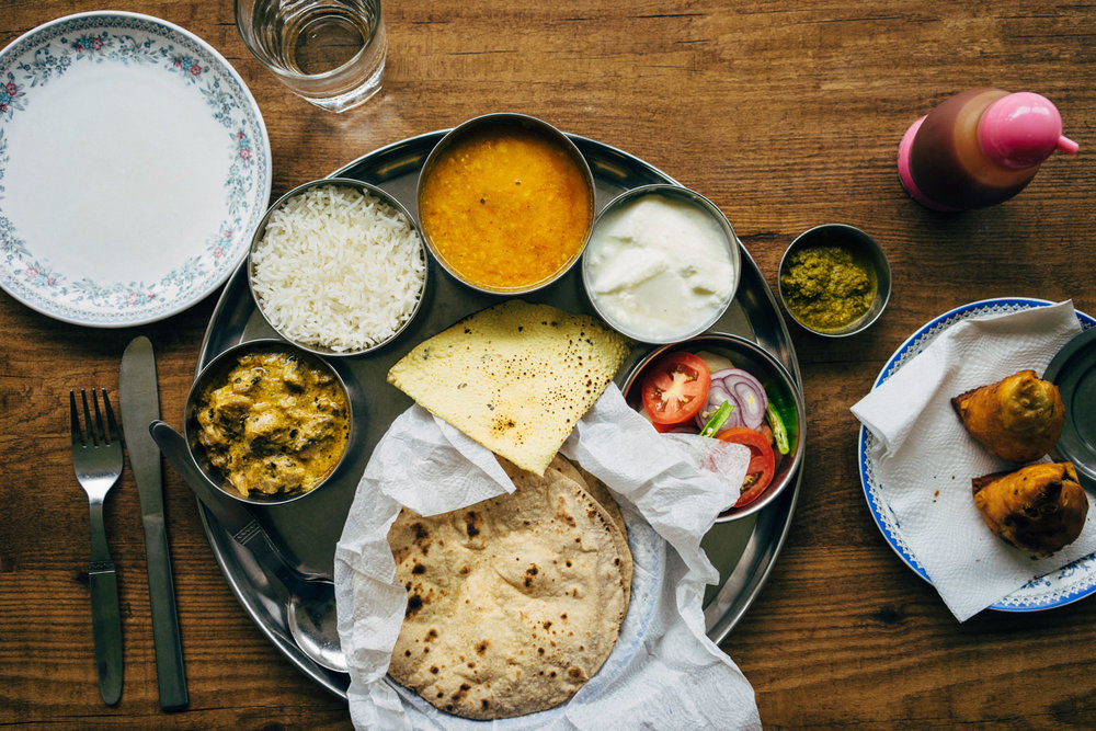 A Northern Indian thali- meal made up of a selection of various dishes and tastes, & samosas.