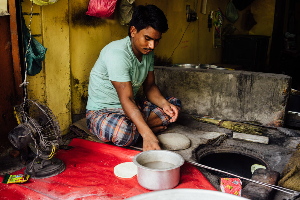 A man making roti in his small street stall.