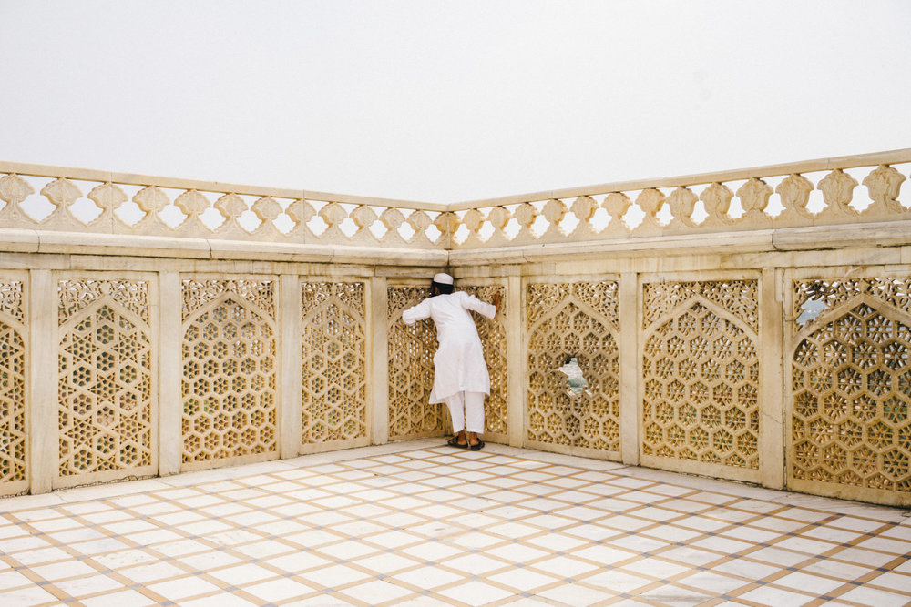 A boy trying to get a glimpse of the Taj Mahal from the Agra Fort.