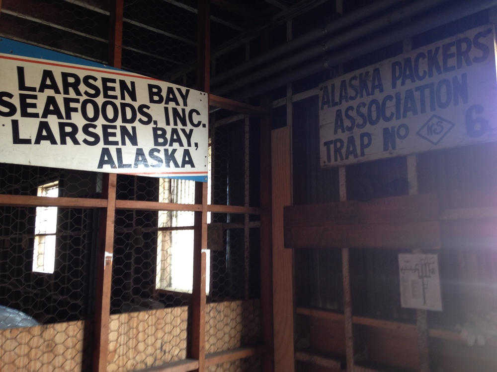 Note the <KS> on the old APA sign on the right. This sign was once hung on a fish trap, but now is visible in the mug up line in the Larsen Bay cannery.