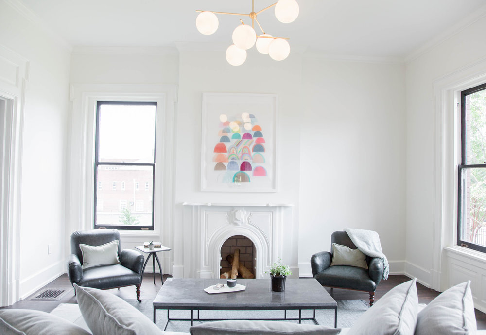 Matte white fireplace in the entry living. Art from Red Arrow Gallery.