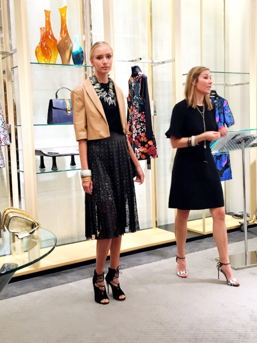 Kristin Jackson (right), Public Relations Director for Neiman Marcus at SouthPark mall, explains some of the Fall trends worn by a model. The model's dramatic eye makeup, bold metallic jewelry and longer, fluid skirt are part of the season's most stylish looks.
