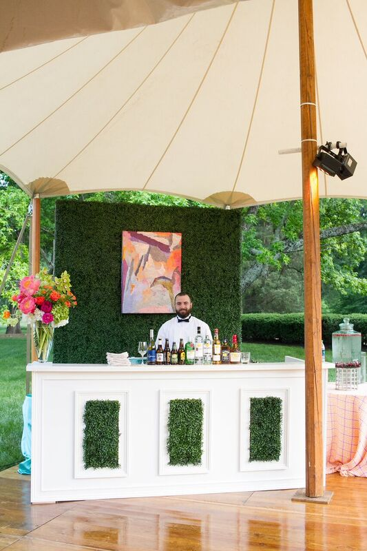 The tent's sides were open to show off the Mint Museum Randolph's vast park-like setting. Bar and cocktail tables were wrapped in boxwood and featured original art work by Herb Jackson, whose works are in the Mint's permanent collection.