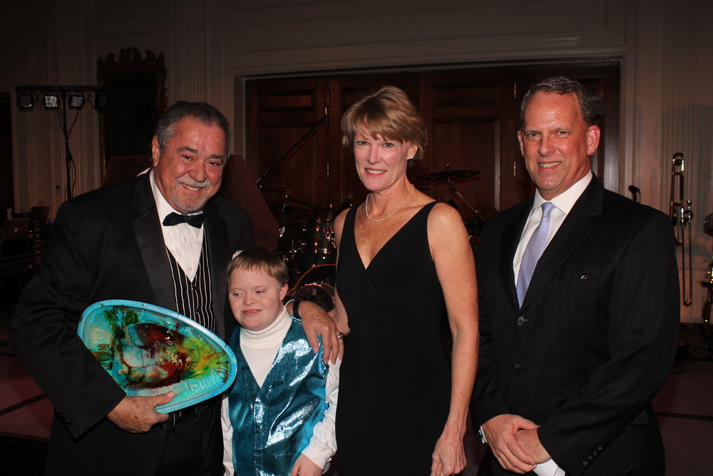 Felix Sabates, left, host of the Ambassador's Ball; Allegro Foundation student Robert; and Robert's parents, Laura and David Short