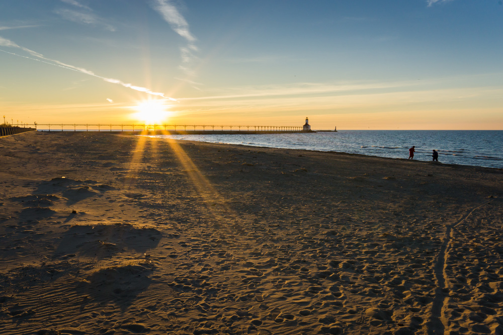 People strolling along Lake Michigan shores at sunset