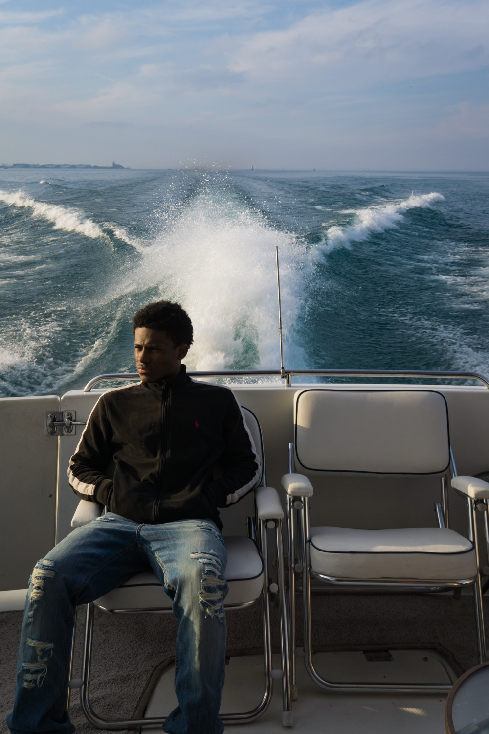 Young man sitting at the stern of the yacht