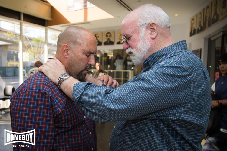 "Fr. Greg Boyle SJ (right) practices ""radical kinship"" with one of the ""homies"" from Homeboy Industries, the world's largest gang prevention, intervention, and re-entry program."
