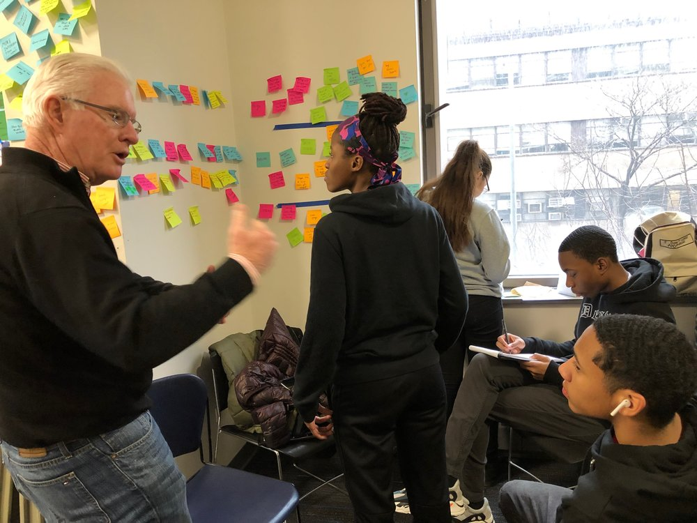 A member of the KIPP team consults with Michael Riordan, a former litigator, while other members of the team do individual research. Later, they will come together as a team to teach one another what they have learned.