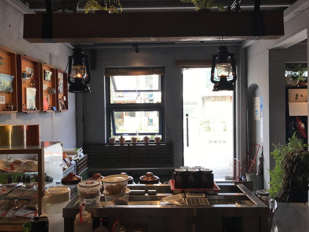 (After>>捨去裝潢,靠佈置完成的櫃檯待客空間。牆上掛著我們店內的四個元素)
