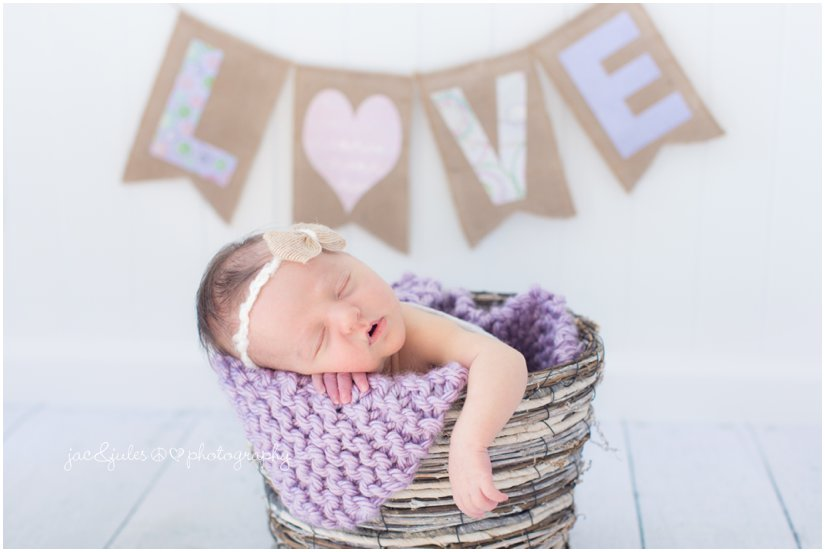 newborn baby girl in basket with purple love banner