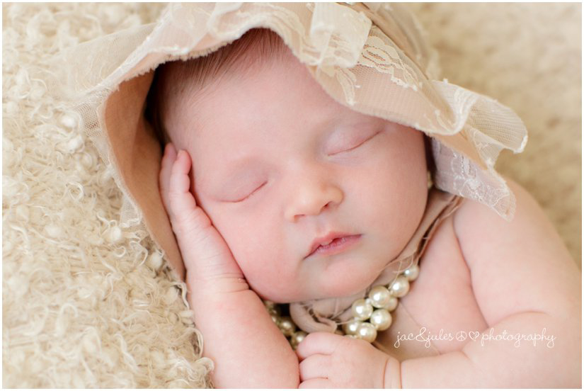 newborn baby girl in pearls and bonnet