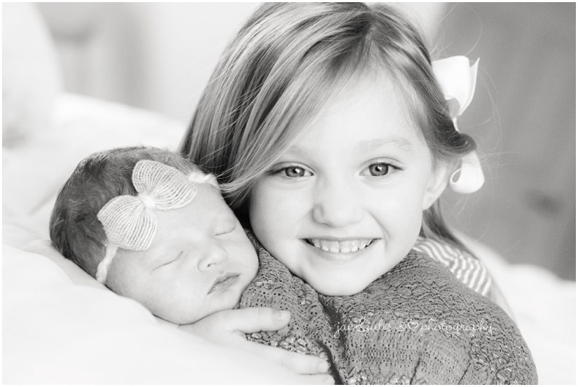 lifestyle newborn baby girl with sister on bed