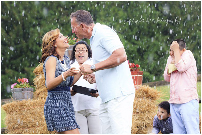 kiss in the rain during outdoor farm wedding ceremony