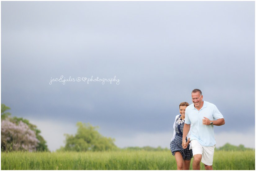 wedding couple running through field from thunderstorm