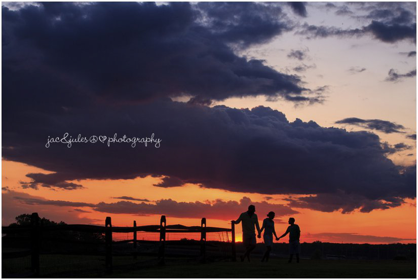 family silhouette against orange and blue sunset on the farm
