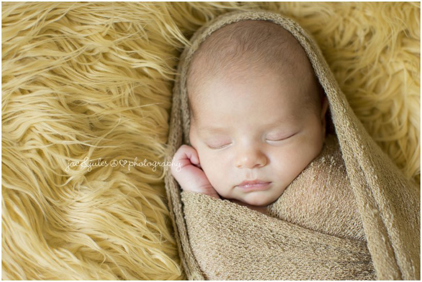 newborn baby wrapped in blanket on fur background