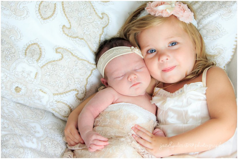 newborn baby girl and sister on bed by professional newborn photographers jacnjules