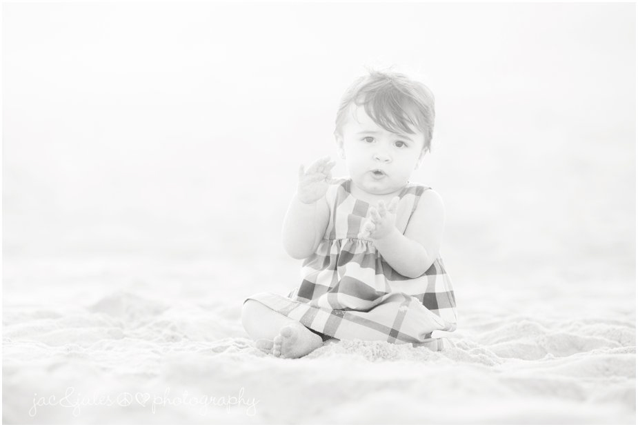 Adorable beach photographs of toddler in her stylish dress with matching red headband shot on Lavallette beach, NJ by JacnJules