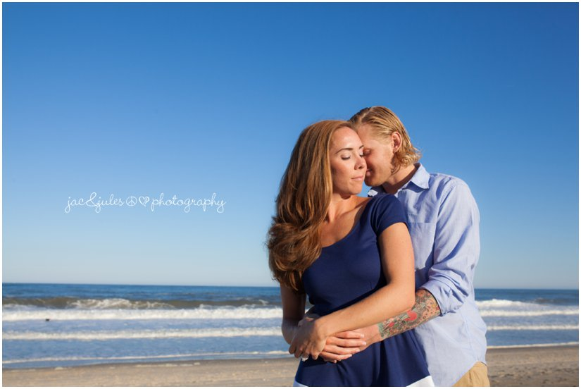 Engaged couple embracing on Manasquan Beach, NJ photographed by JacnJules