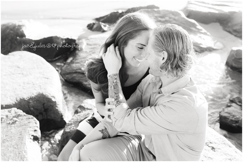 Black and white engagement photo of the jetty in Manasquan Beach, NJ by JacnJules