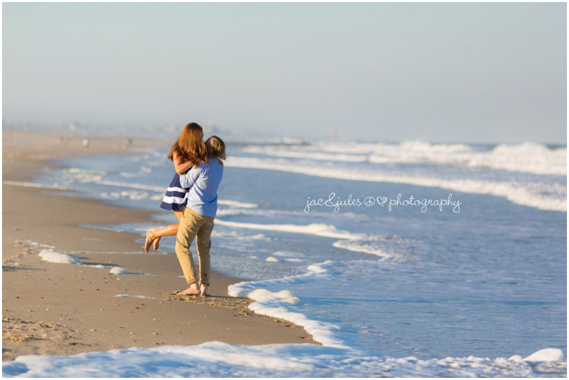 Romantic photograph of engaged couple lifting his bride to be on Manasquan Beach, NJ photographed by JacnJules
