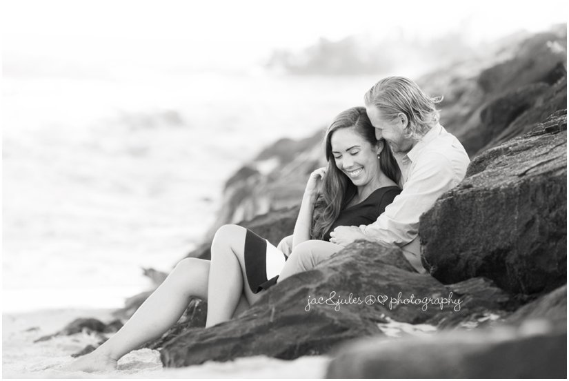 black and white of engaged couple on the jetty in Manasquan Beach in NJ  by JacnJules