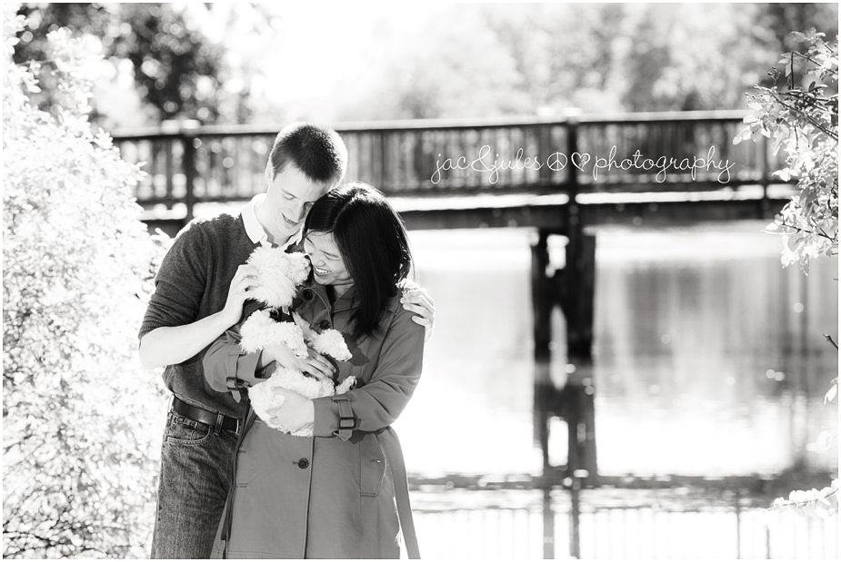 black and white of an engaged couple and their puppy in front of Lake Packanack in Passaic County, NJ by JacnJules