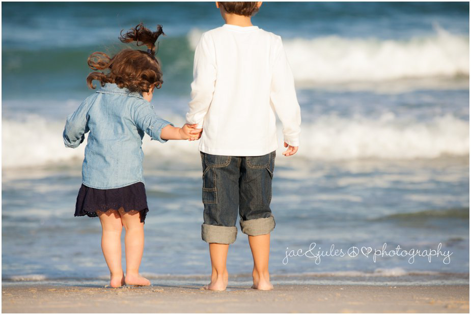 Brother and sister holding hands watching the waves on Lavallette Beach, NJ by JacnJules