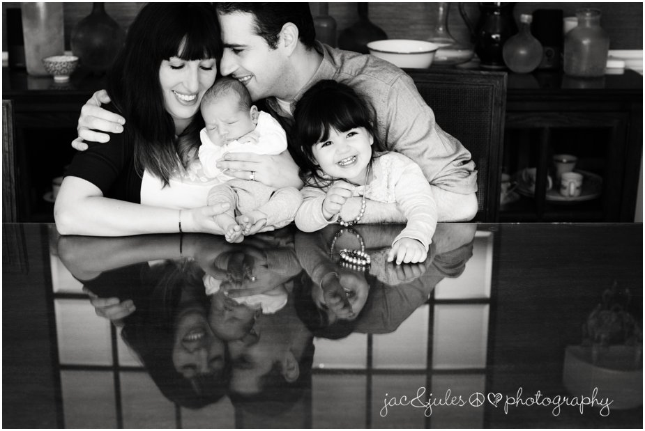 Black and white photo taken in home of newborn with his family photographed by JacnJules in Monmouth, NJ