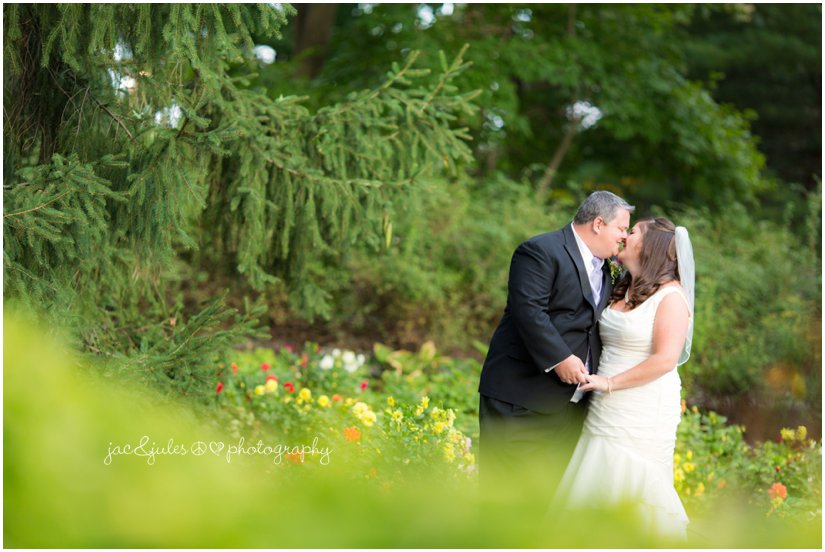 Bride and groom stealing a kiss photographed at the Mansion at Bretton Woods in Morristown, NJ by JacnJules