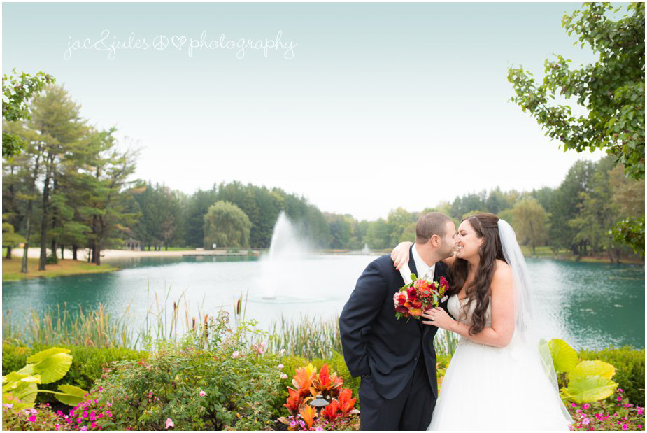 Gorgeous photo of bride and groom in front of lake at Frogbridge in Millville, NJ photographed by JacnJules