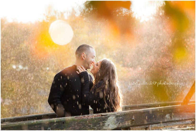 Cute couple kissing in the rain during engagement session at Spring Lake in NJ photographed by JacnJules
