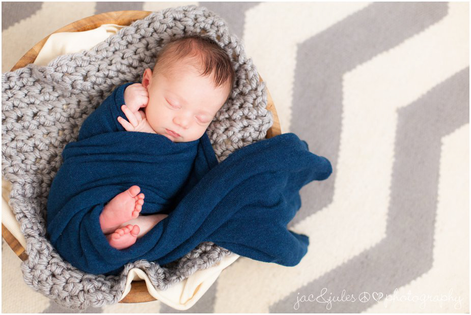 picture of a newborn baby in a bowl with a chevron rug