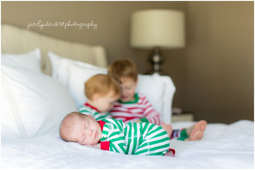 holiday sibling newborn photos on the bed at home in rumson, nj