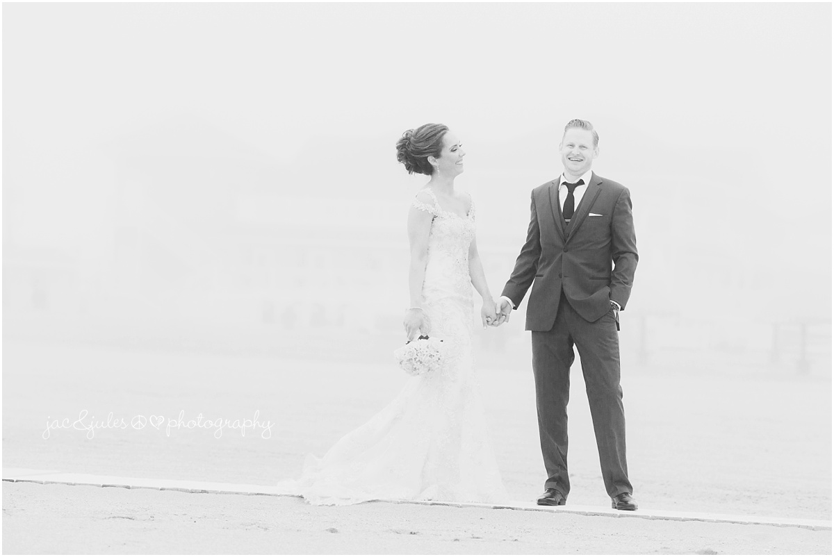 black and white of bride and groom on beach in fog