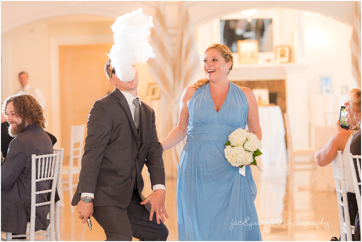 groomsman makes smoke cloud during reception entrance
