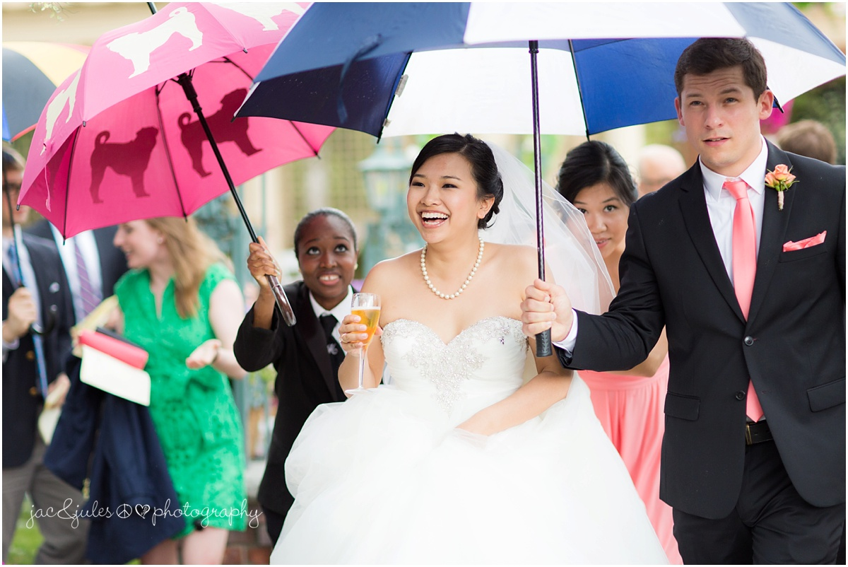bride under umbrella with champagne running from thunderstorm during outdoor wedding ceremony