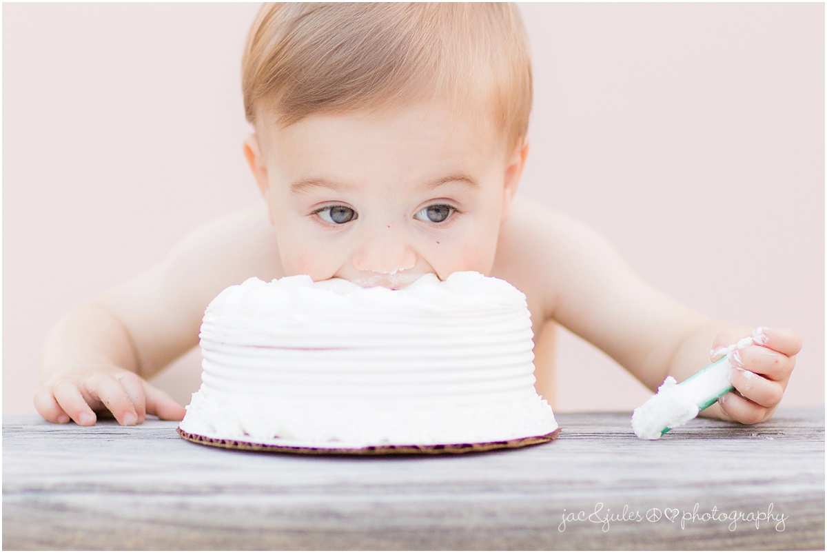 baby dives mouth first into cake for first birthday.