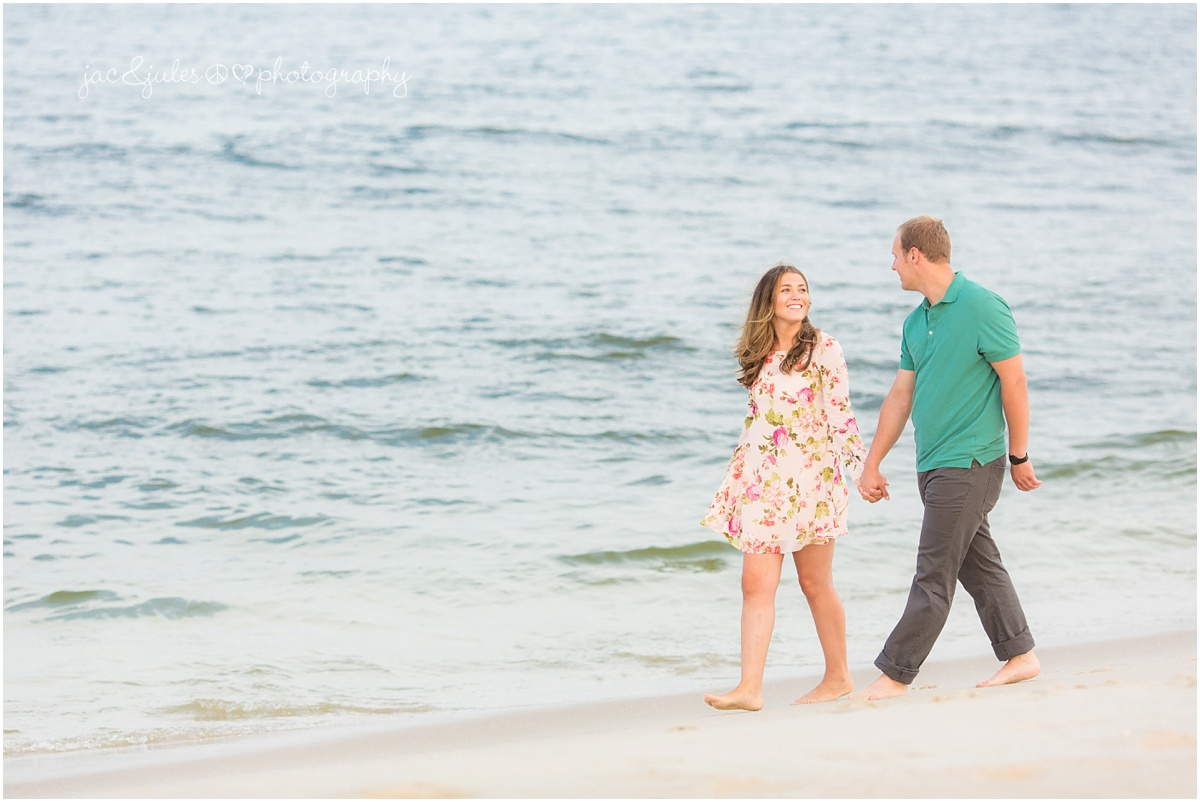 engaged couple walking along the water on the beach
