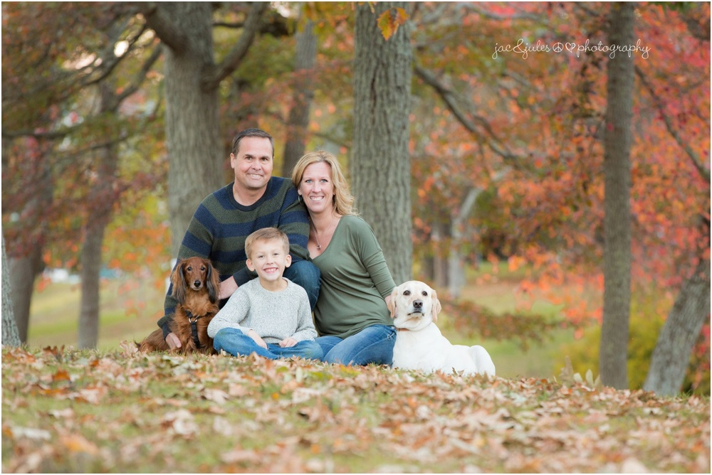 family of 3 with 2 puppy dogs in the fall leaves