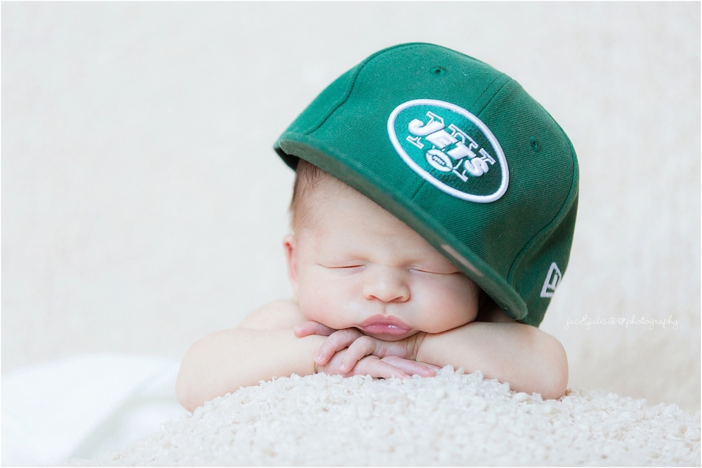 jacnjules photographs newborn boy with a Jets football hat in manalapan, nj