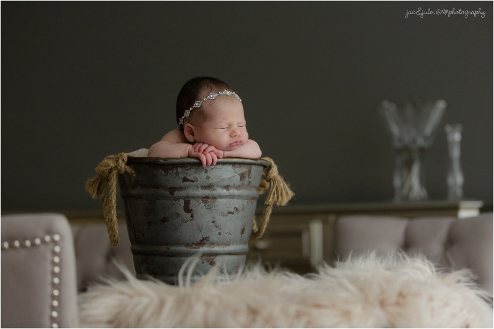 newborn baby girl in jeweled headband and metal bucket