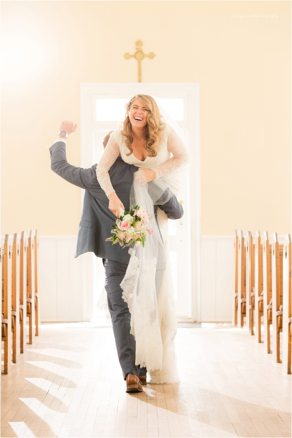 groom carrying bride down the aisle over his shoulder.  fun church photo