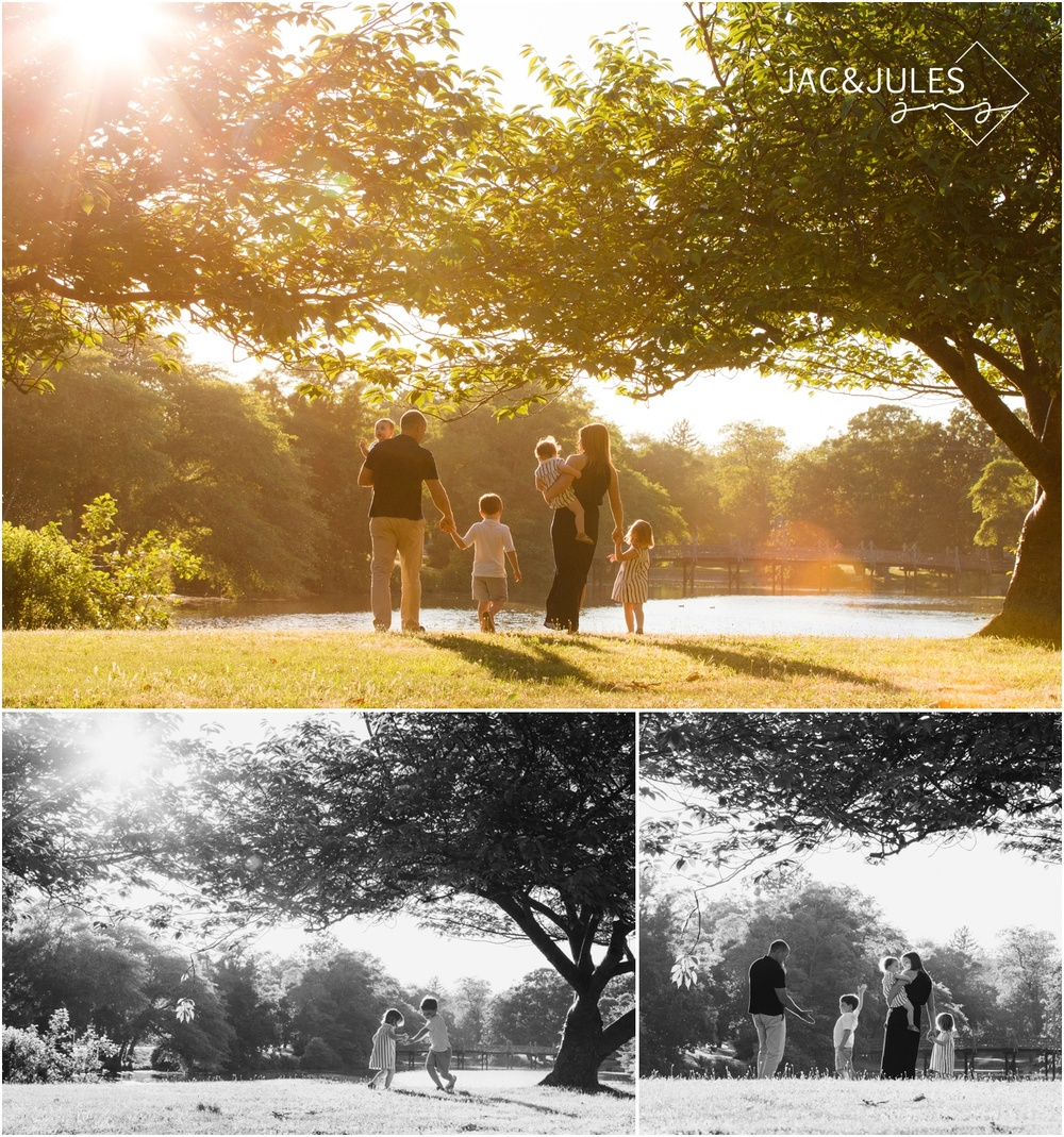 sun drenched photo of family walking by spring lake with sun flare.  Son gives dad a high-5